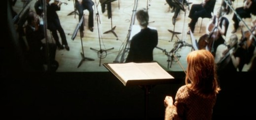 A woman conducts along to a filmed orchestra.