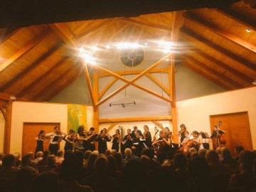 A large ensemble performs in front of a crowd in the Yellow Barn