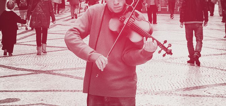 A violinist plays in the street as pedestrians pass by