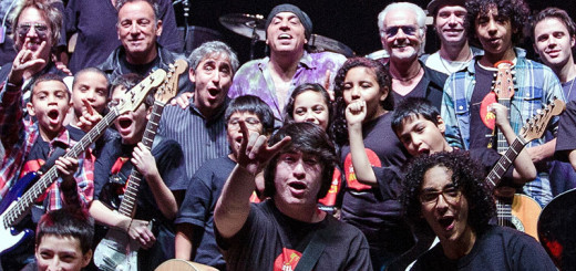 David Wish with Steve Van Zandt amongst kid guitarists from Little Kids Rock make rock hand gestures and expressions