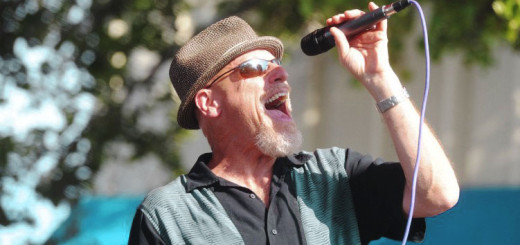 A man sings into a microphone. Trees branches hang in the background.