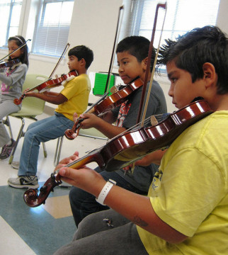 Young kids play violin in a classroom
