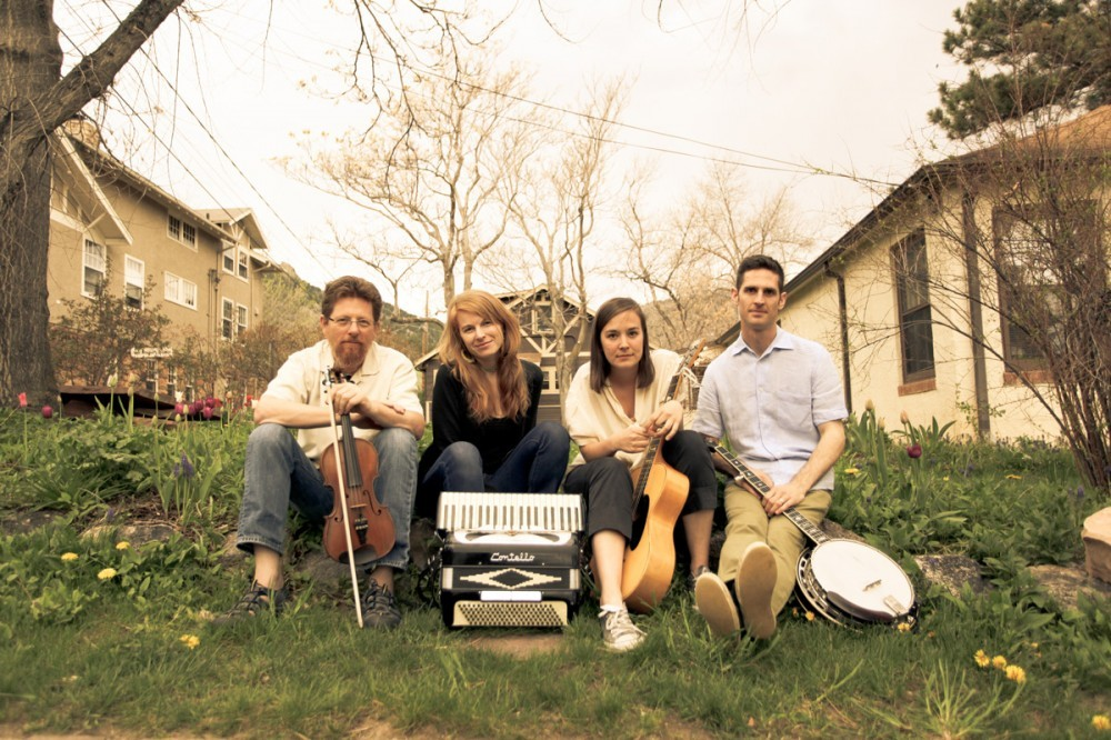 The Lomax Project members sit among houses with their instruments