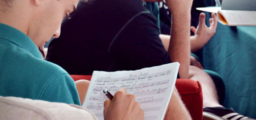 A young man writes on sheet music while other youths chat in the background