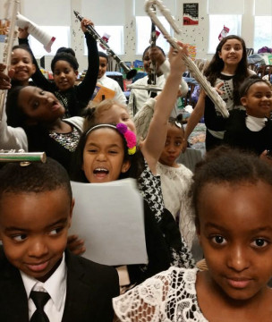 Kids raise instruments into the air in a classroom
