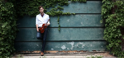 Blake Pouliot holds his violin, standing against a wall
