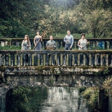 City of Tomorrow band members stand on a moss-covered bridge in a swamp