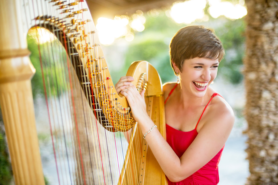 A woman smiles and leans on her harp