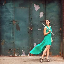 A flutists stands against a rusty green door