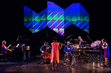 Musicians perform in front of an abstract image