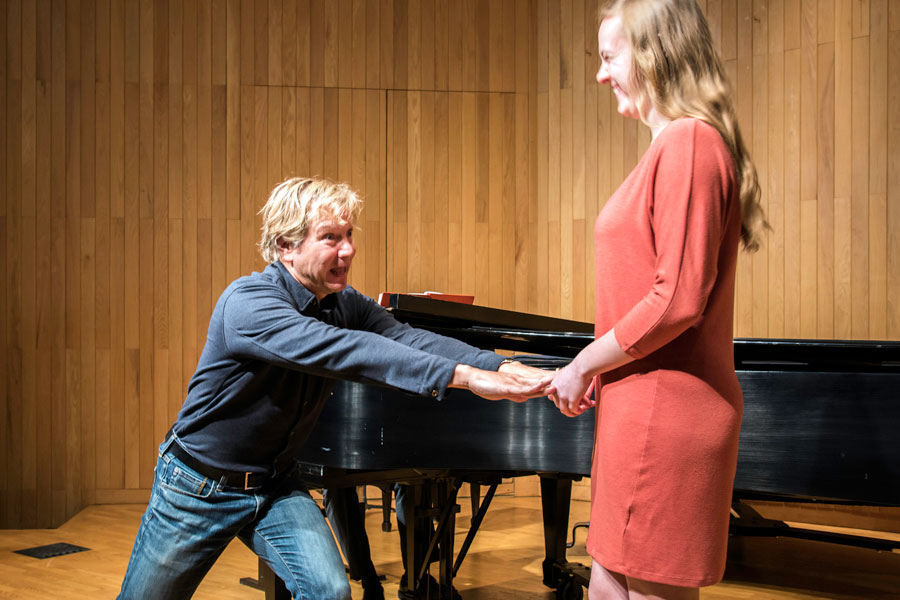 Mark Adamo grasps DePauw student Shannon Barry's hands as they stand before a grand piano