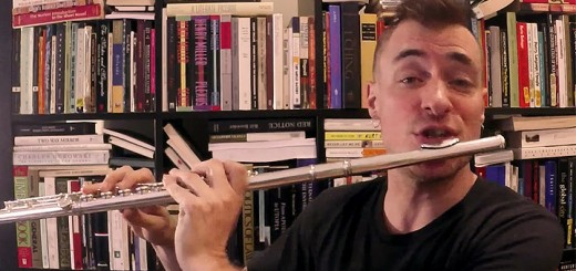 Greg Pattillo plays the flute in front of a full book shelf