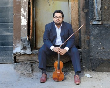 Vijay Gupta sits on the step of a dilapidated building with his violin. Photo by Gary Leonard.
