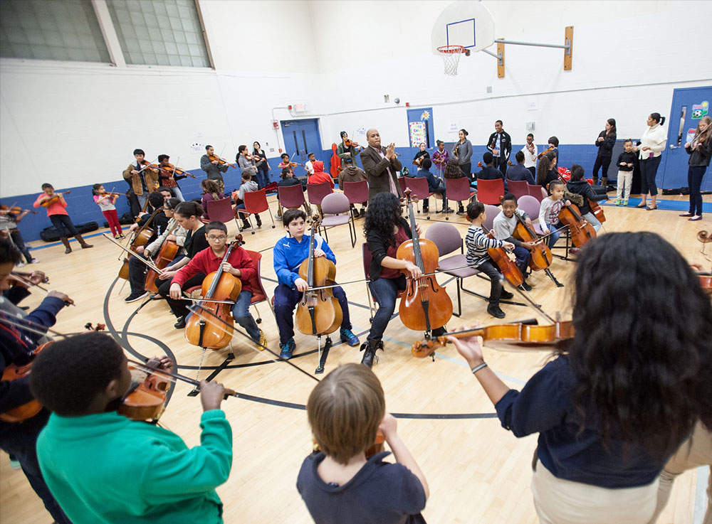 Kids play instruments in a gymnasium