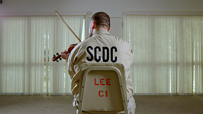 An inmate plays the violin