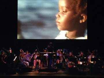 An orchestra performs in front of a projection