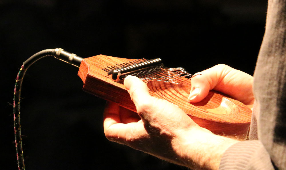 Close-up of hands playing the Electric Mbira