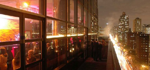 People socialize in the Stanley H. Kaplan Penthouse against the New York City skyline
