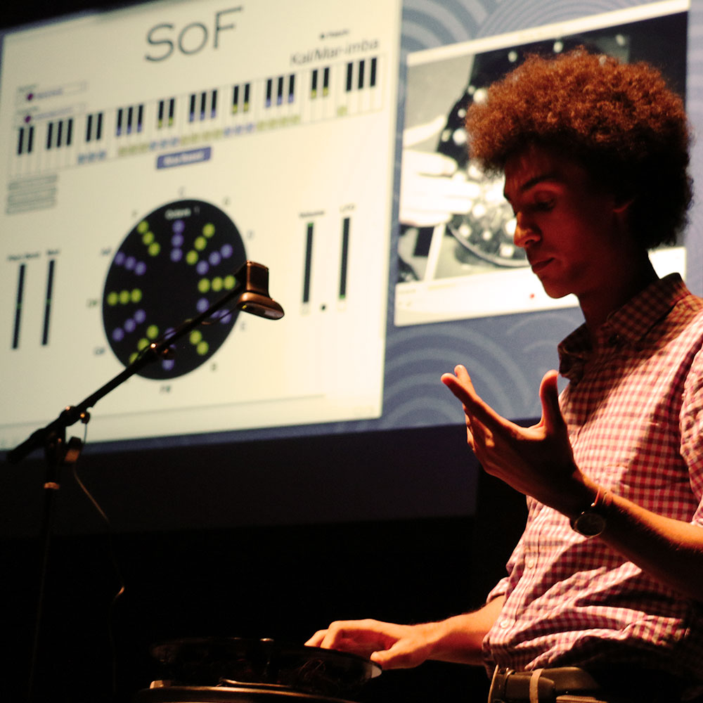 Ruben Dax Sonz-Barnes demonstrates the Spiral of Fifths against the backdrop of a projected diagram of the instrument