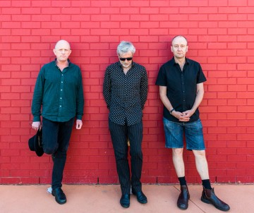 The Necks stand against a red brick wall