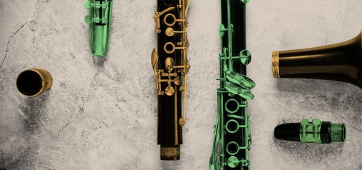 Yellow and green parts of a clarinet sit on a rough background