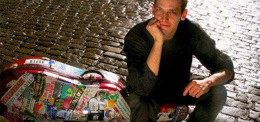 Mike Block sits on his sticker-covered cello case on a brick street