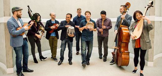 A diverse group of musicians stand in line with their instruments