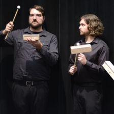 The four members of Rela Percussion stand next to each other with wood blocks and mallets