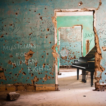 A grand piano sits in a bullet-riddled room