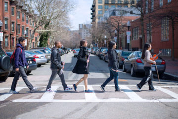 Student musicians walk through a crosswalk