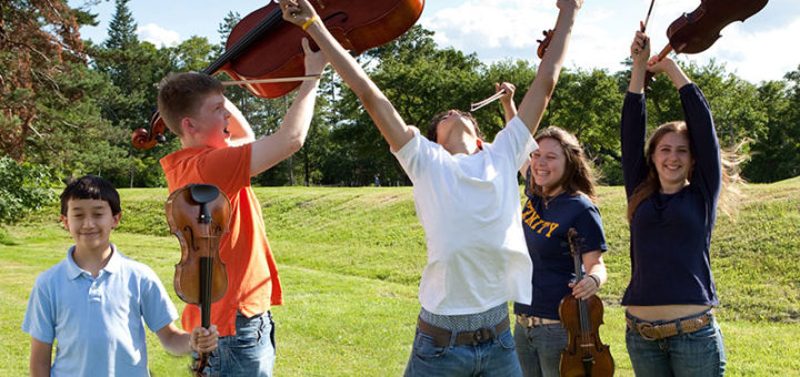 Student musicians hold their instruments up in the air