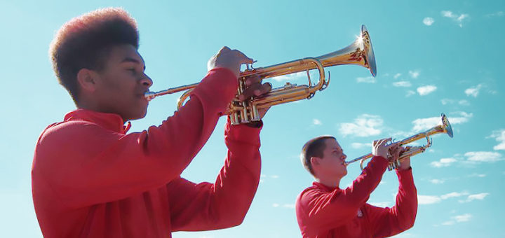 Two young men play trumpets