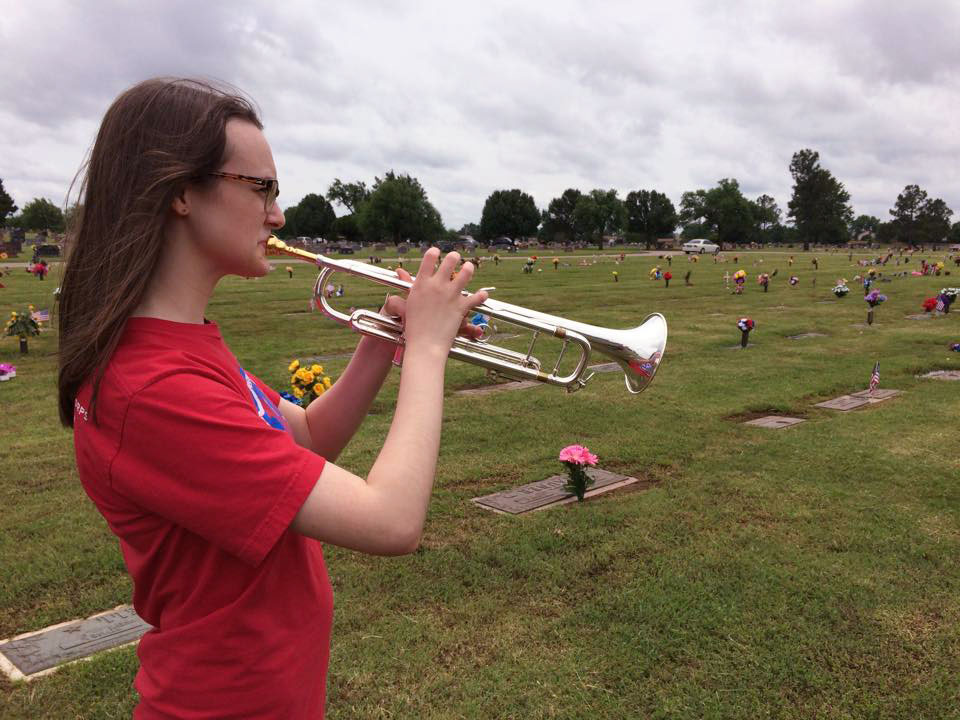 Katie Prior plays the trumpet at a cemetery