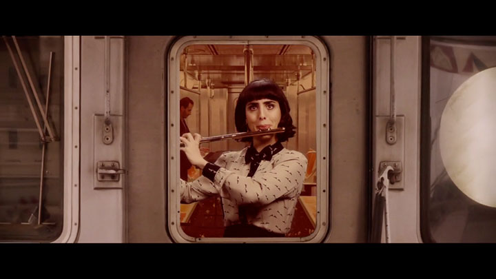 A flautist plays on a stylized subway car
