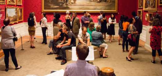 A drummer plays in a museum gallery