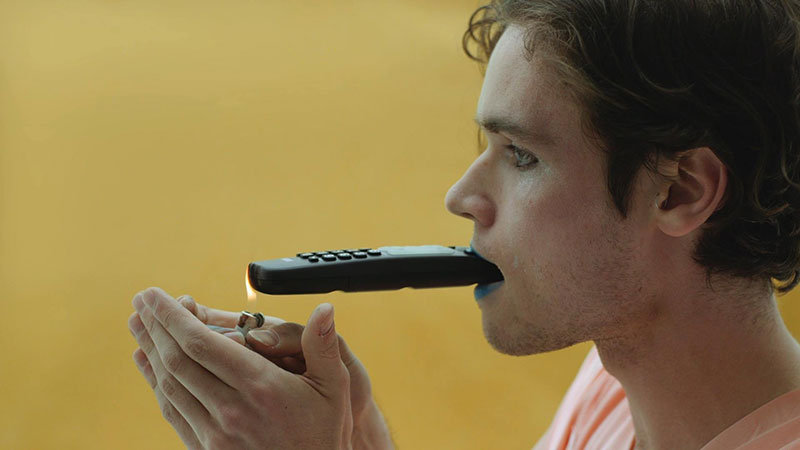 A man lights a remote control in his mouth