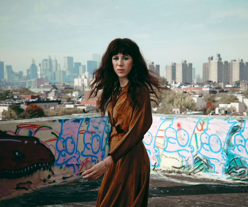 Missy Mazzoli stands in front of graffiti