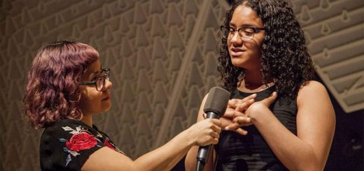 A woman holds a microphone up to another woman