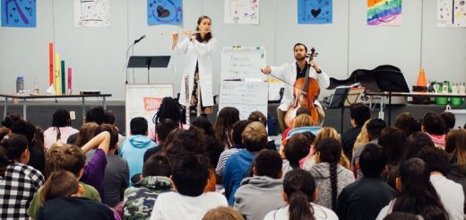 Kids watch a flutist and cellist perform in a classroom