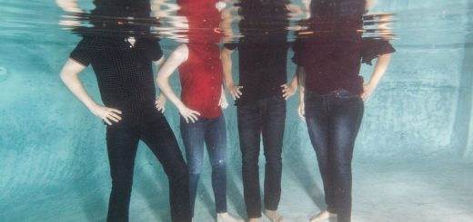 Four people, clothed, underwater