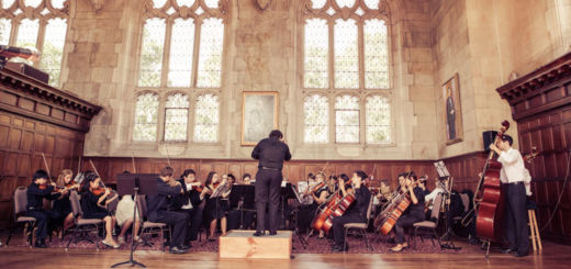 An orchestra performs in an old concert hall