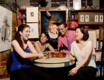 Carpe Diem String Quartet sit around a table at a small grocery store, a painting of John Wayne hanging behind them