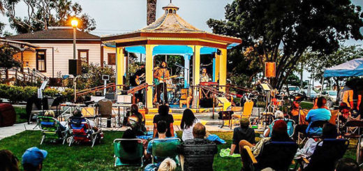 People sit on the grass and listen to a band play in a gazebo