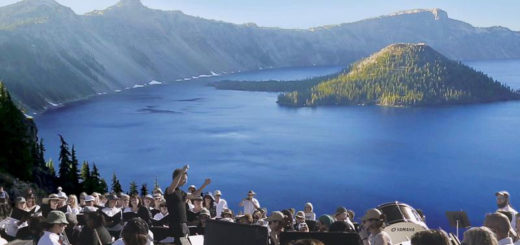 A symphony performs in front of a lake and mountains