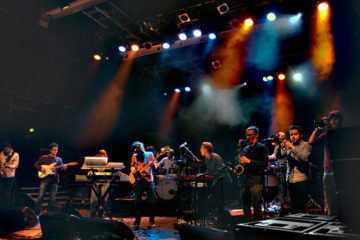 A big group of musicians perform on stage