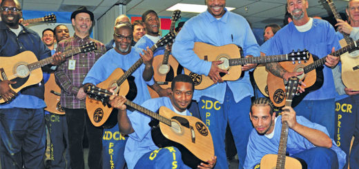 Inmates hold up their acoustic guitars