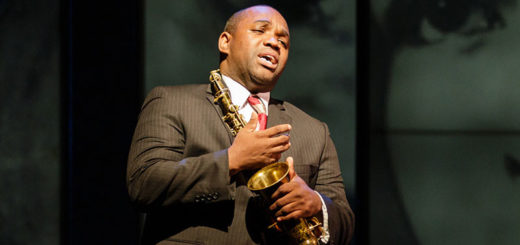 A man playing Charlie Parker holds a saxophone