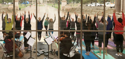 People practice yoga in front of a chamber orchestra
