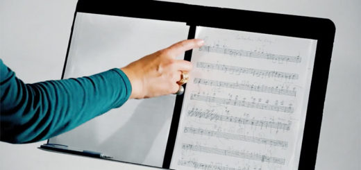 A hand points at a composition sheet on a music stand