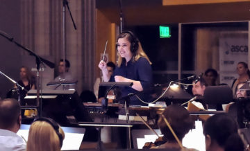 A conductor wears headphones in a studio and conducts an orchestra